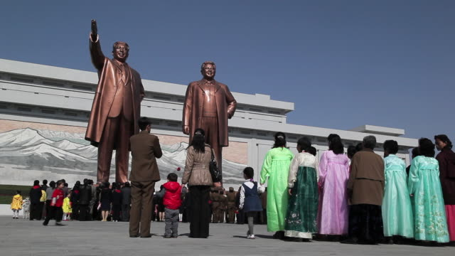 respectful koreans bring flowers as they visit the mansudae grand monument on mansu hill and view the statues of former presidents kim il-sung and kim jong il. - north korea stock videos & royalty-free footage