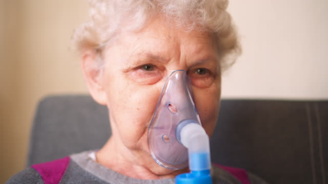 respiratory oxygen nasal catheter to senior woman - inhaling stock videos & royalty-free footage