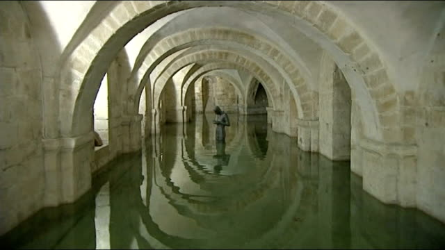 respite from storms / impact of damage; winchester cathedral: int flooded crypt of winchester cathedral partially submerged statue in crypt - cathedral stock videos & royalty-free footage