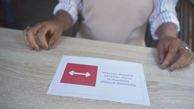 responsible female coffee shop worker gluing a information sign on coffee shop table about rule of 2 meters apart - information sign stock videos & royalty-free footage