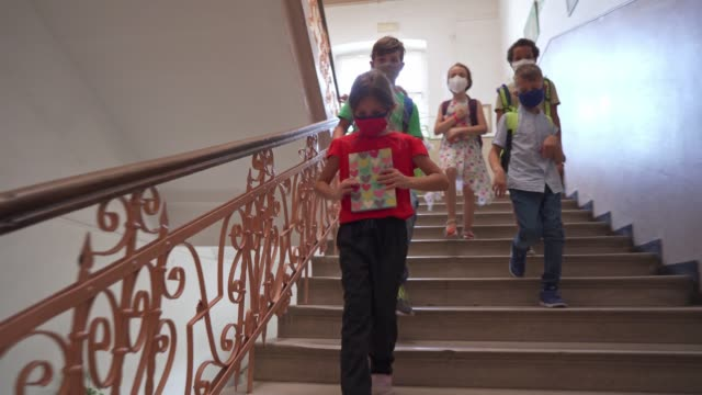 responsible group of multiracial elementary school kids going down the stairs for their class while wearing protective face mask and keeping social distancing - reopening stock videos & royalty-free footage
