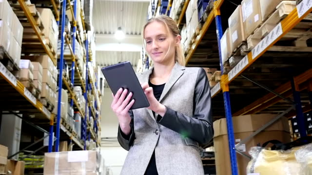 Responsible manager working on tablet in warehouse