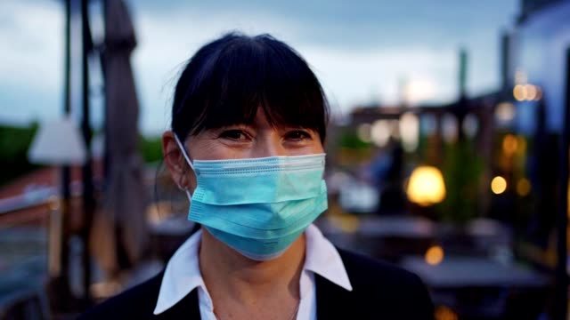 responsible senior businesswoman wearing protective face mask during coronavirus pandemic at a business meeting - formal businesswear stock videos & royalty-free footage