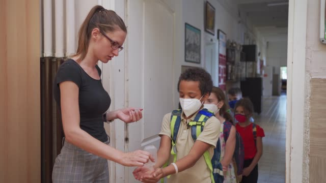 responsible teacher trying to educate her students and help them about their safety at school during coronavirus pandemic - school supplies stock videos & royalty-free footage