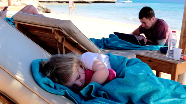 rest on the red sea in egypt. the child is sleeping and the father is working on a laptop. - towel stock videos & royalty-free footage