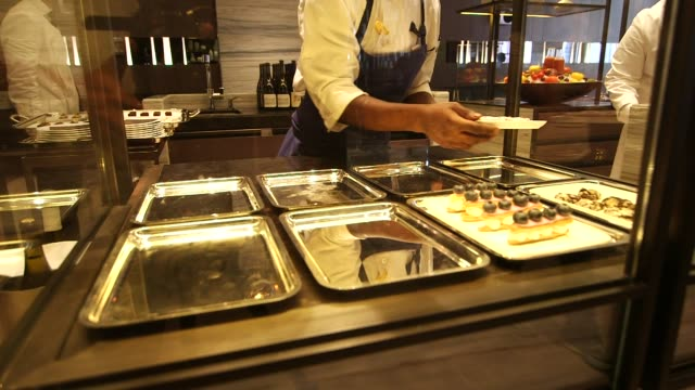 vídeos de stock e filmes b-roll de restaurant and kitchen at the park hyatt hotel in new york ny on august 26 2014 restaurant interiors and customers sitting at tables a chef adds... - equipamento doméstico