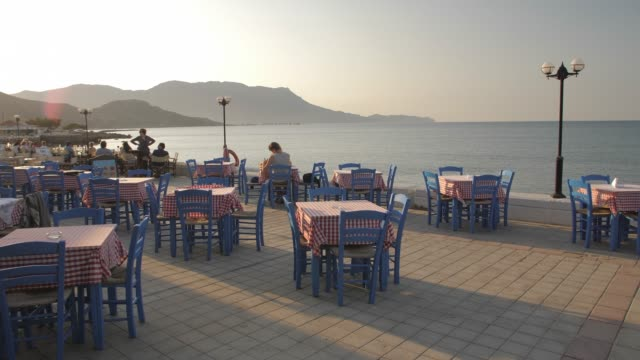 restaurant at paraliaki promenaad at sunset in kissamos, crete, greek islands, greece, europe - mediterranean culture stock videos & royalty-free footage