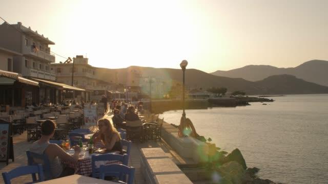 restaurant at paraliaki promenaad at sunset in kissamos, crete, greek islands, greece, europe - mediterranean culture stock videos & royalty-free footage
