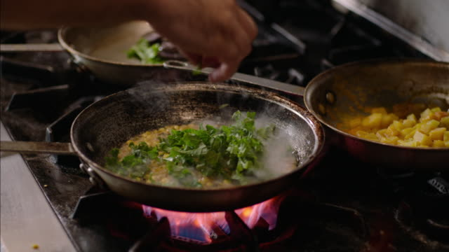 restaurant chef adds greens to corn succotash mix and flips over flaming skillet in kitchen - gourmet küche stock-videos und b-roll-filmmaterial