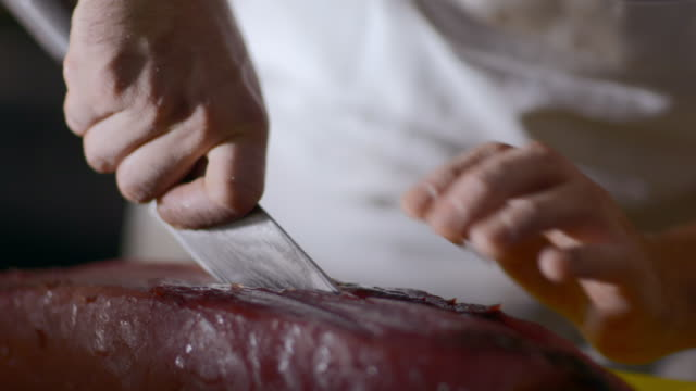 restaurant chef cuts thick slab of tuna steak on chopping block in restaurant kitchen - seafood stock videos & royalty-free footage