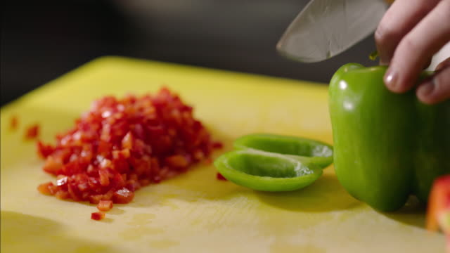 Restaurant chef slices green bell pepper on chopping block in restaurant kitchen