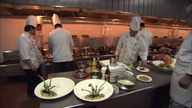 a restaurant chef tastes a small plate of food in a busy kitchen. - hat stock videos and b-roll footage