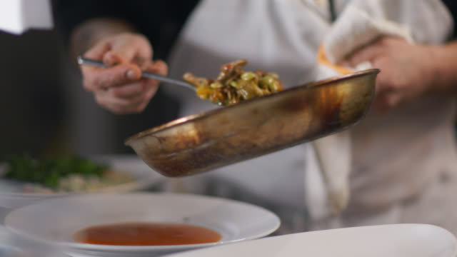 restaurant chef tosses fresh-made succotash in pan and serves on dinner plate in kitchen - gourmet küche stock-videos und b-roll-filmmaterial