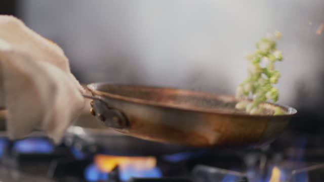 Restaurant cook flips vegetables in flaming skillet in restaurant kitchen