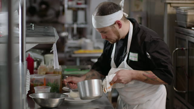 Restaurant cook spreads sauce around dinner plate as chef prepares dishes of steaming scallops in kitchen