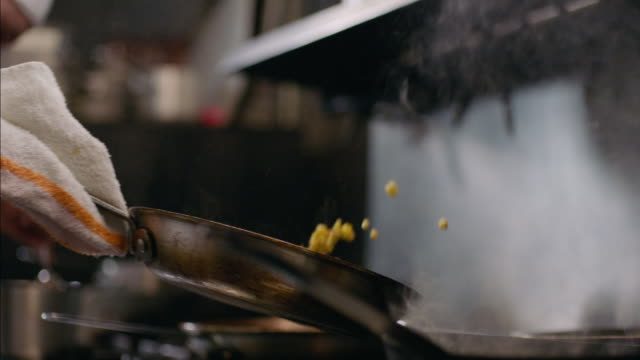 Restaurant cook tosses corn in iron skillet over stove top in slow motion
