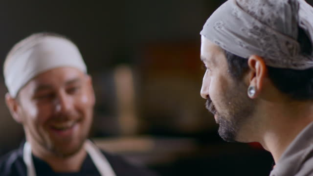 vidéos et rushes de restaurant cooks chat in kitchen and smell hot chili peppers - piment