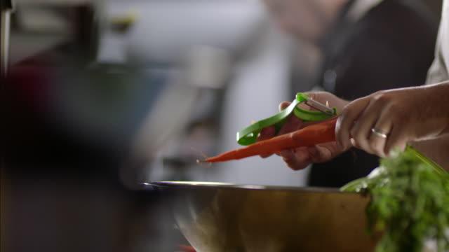 vídeos de stock, filmes e b-roll de restaurant cooks peel carrots in busy kitchen restaurant - vegan