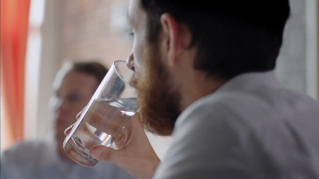 Restaurant employee drinks glass of water as boss leads team meeting