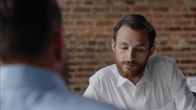 vídeos de stock e filmes b-roll de restaurant employee listens to boss and offers input in team meeting - employee