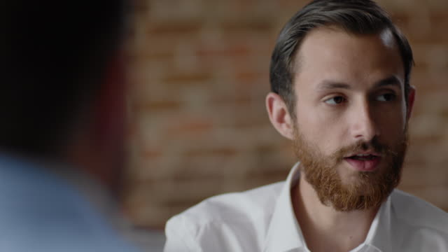 Restaurant employee speaks confidently with boss in staff meeting