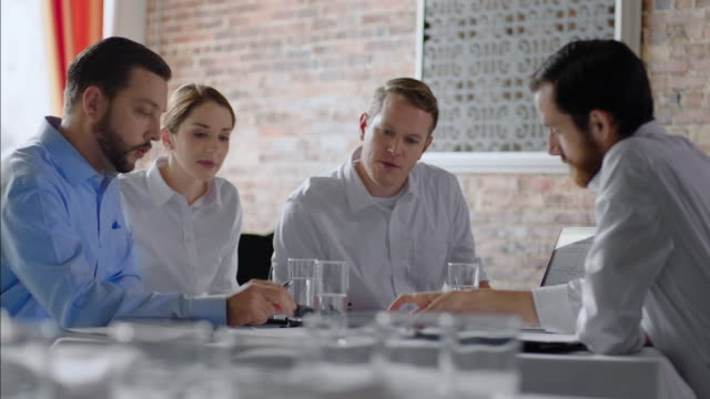 Restaurant employees discuss paperwork with boss in staff meeting