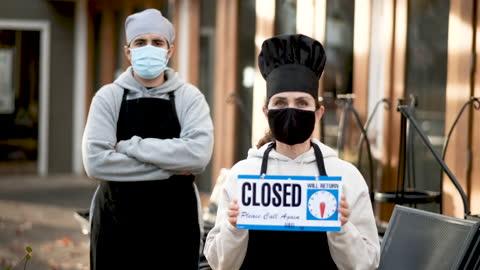vídeos de stock e filmes b-roll de restaurant employees holding a closed sign wearing protective face masks - falência