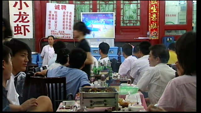 restaurant exterior with bright flashing neon sign int chinese people eating at restaurant tables watching olympic coverage on televisions and... - pink shirt stock videos and b-roll footage