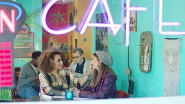 Restaurant hostess seats two young women on lunch date in local cafe.