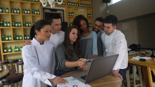 Restaurant manager explaining to her team something while pointing at laptop