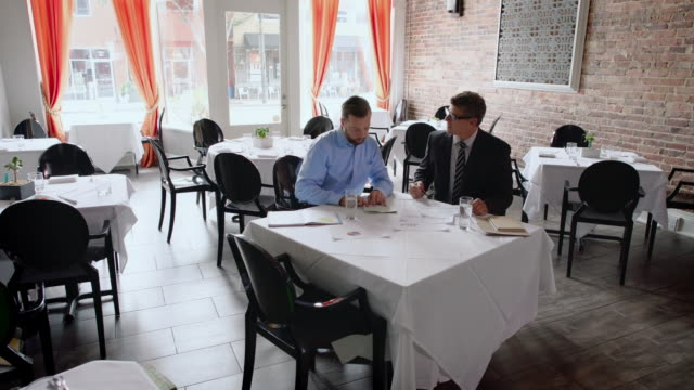 restaurant owner discusses business with financial advisor - gastwirt stock-videos und b-roll-filmmaterial