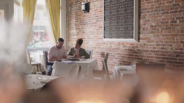 vídeos de stock e filmes b-roll de a restaurant owner discusses finances with a financial analyst at a table - artigo de decoração