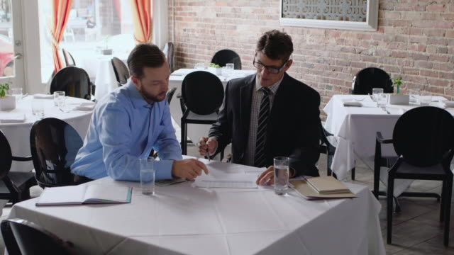 vídeos de stock, filmes e b-roll de restaurant owner discusses paperwork with financial advisor in business meeting - financial accessory