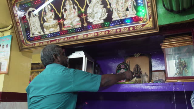 Restaurant owner from India doing religious offering to Hinduism gods