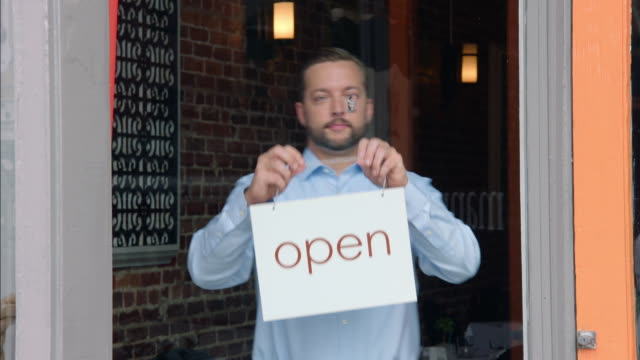 Restaurant owner hangs and adjusts open sign on door of downtown storefront