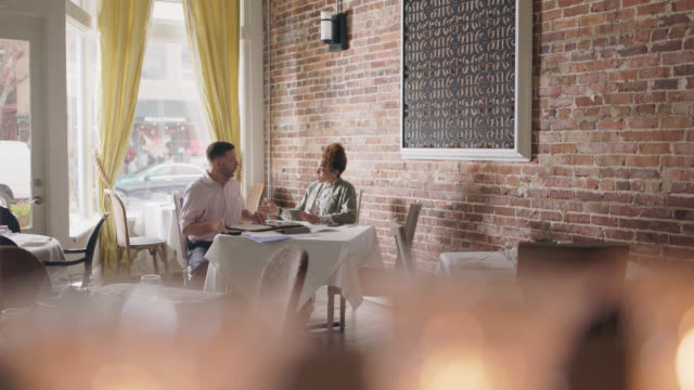 a restaurant owner sits down with a financial analyst at a table inside his restaurant - analysing stock videos & royalty-free footage