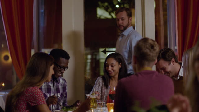 Restaurant owner stops by table to greet and chat with happy dinner party