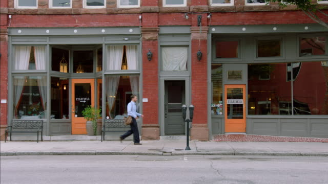 vídeos de stock, filmes e b-roll de restaurant owner walks down sidewalk and unlocks business storefront - exterior