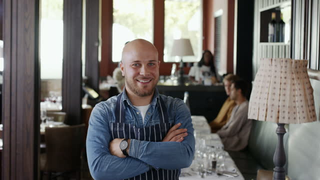 restaurant owner wearing apron smiling towards camera - business stock videos & royalty-free footage