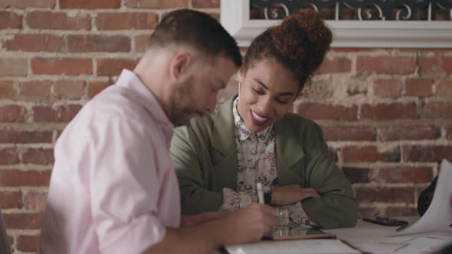 restaurant owners sign financial paperwork with a female financial analyst - analysing stock videos & royalty-free footage