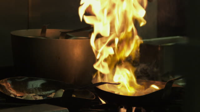 Restaurant saute pans catching fire as alcohol burns off.