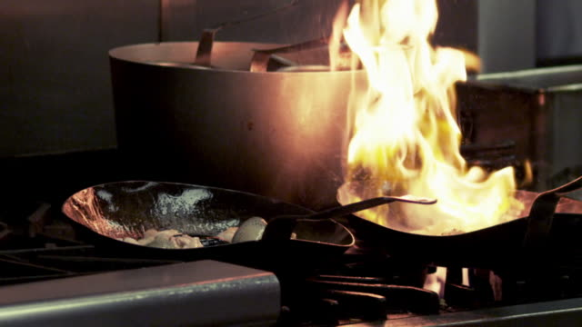 restaurant saute pans catching fire momentarily then being stirred. - saute stock videos and b-roll footage