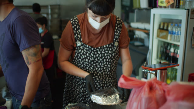 restaurant staff bagging delivery orders during covid-19 lockdown - taco stand stock videos & royalty-free footage