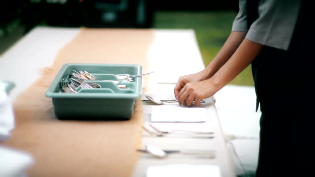 Restaurant staff setting outdoor table for dinner party or wedding reception.