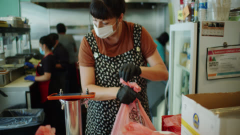 restaurant staff wearing masks and gloves at work during covid-19 lockdown assembling orders for pick-up and delivery - fast food stock videos & royalty-free footage