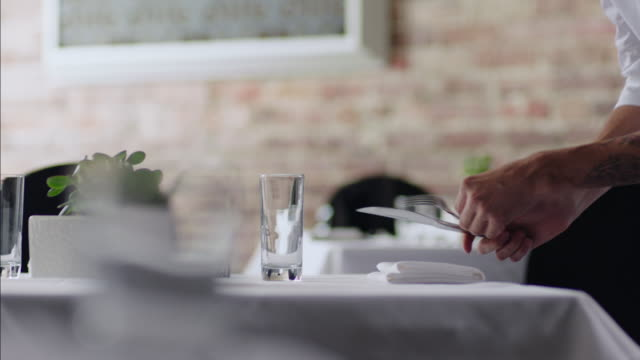 restaurant waiter arranges silverware with precision - arranging stock videos and b-roll footage
