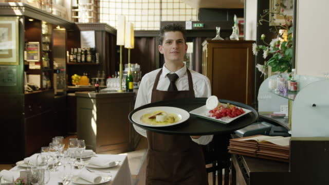 ds restaurant waiter following camera carrying tray with plates looking to camera - plate stock videos and b-roll footage