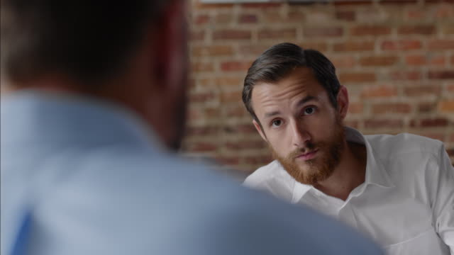 Restaurant waiter listens to instructions from boss during daily meeting