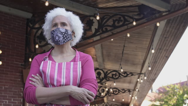 restaurant wearing a protective mask standing in front of her business - street name sign stock videos & royalty-free footage