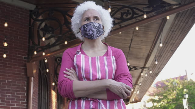 restaurant wearing a protective mask standing in front of her business - in front of stock videos & royalty-free footage